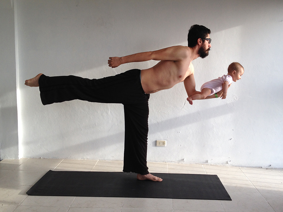 man going yoga while holding his baby